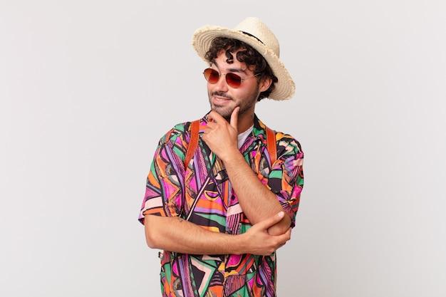 Uomo turistico ispanico che sorride con un'espressione felice e sicura con la mano sul mento, chiedendosi e guardando di lato
