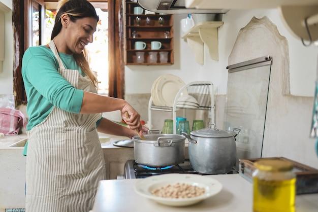 Donna ispanica che cucina all'interno della cucina vintage a casa - felice chef femminile che si diverte a preparare il pranzo durante la mattina - focus a portata di mano