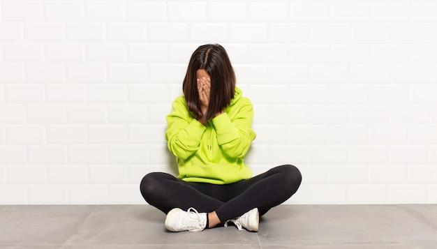 Donna ispanica che copre gli occhi con le mani con uno sguardo triste e frustrato di disperazione, pianto, vista laterale