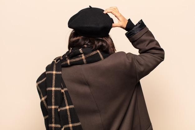 Donna ispanica che si sente incapace e confusa, pensando a una soluzione, con una mano sull'anca e l'altra sulla testa, vista posteriore