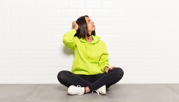Donna ispanica che si sente incapace e confusa, pensando a una soluzione, con una mano sul fianco e l'altra sulla testa, vista posteriore