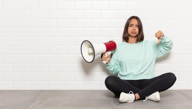 Donna ispanica che si sente arrabbiata, arrabbiata, infastidita, delusa o scontenta, mostrando i pollici verso il basso con uno sguardo serio