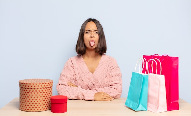 Donna ispanica che si sente disgustata e irritata, sporge la lingua, non ama qualcosa di sgradevole e schifoso