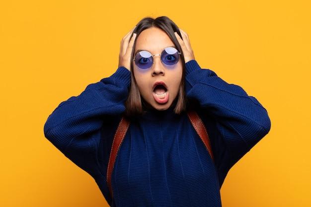 Donna ispanica che si sente inorridita e scioccata, alza le mani alla testa e si fa prendere dal panico per un errore