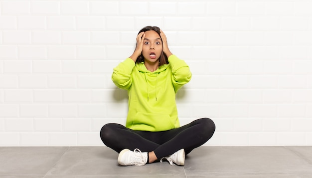 Donna ispanica che si sente inorridita e scioccata, alzando le mani alla testa e in preda al panico per un errore
