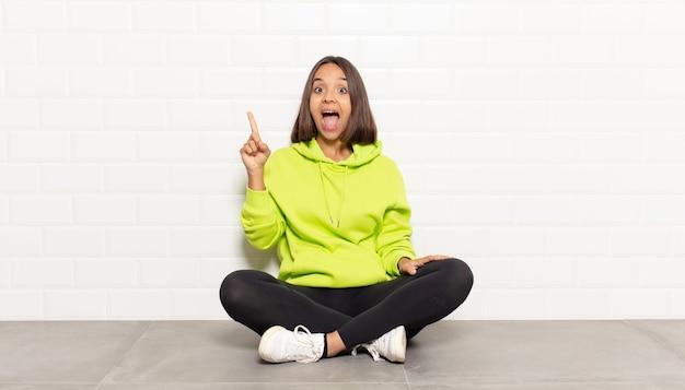 Donna ispanica che si sente un genio felice ed eccitato dopo aver realizzato un'idea, alzando allegramente il dito, eureka!