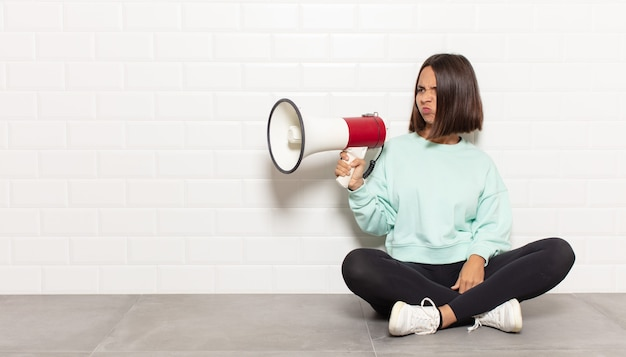 Donna ispanica che si sente triste, turbata o arrabbiata e guarda di lato con un atteggiamento negativo, aggrottando la fronte in disaccordo