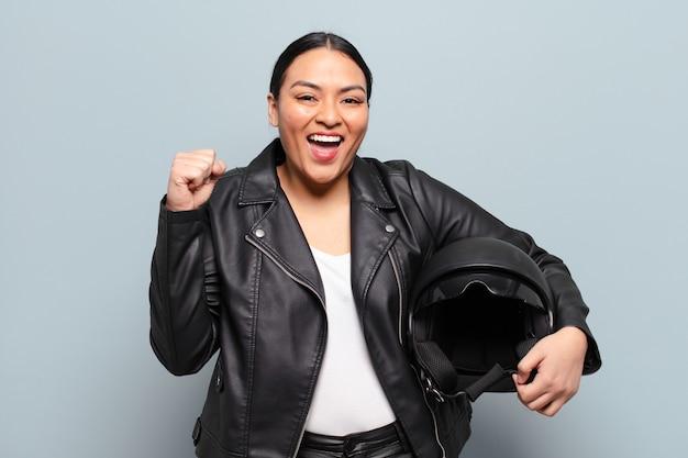 Donna ispanica che si sente scioccata, eccitata e felice, ride e celebra il successo, dicendo wow!
