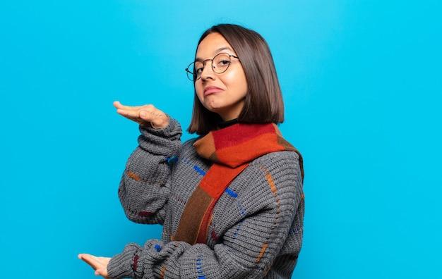Donna ispanica che tiene un oggetto con entrambe le mani sullo spazio della copia laterale