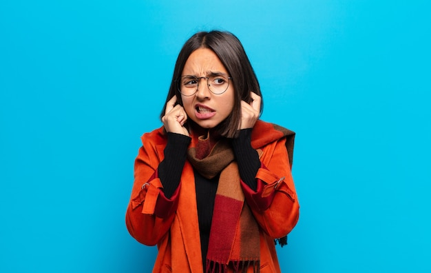 Donna ispanica che sembra arrabbiata, stressata e infastidita, coprendo entrambe le orecchie con un rumore assordante, un suono o una musica ad alto volume