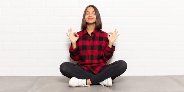 Donna ispanica che sembra concentrata e medita, si sente soddisfatta e rilassata, pensa o fa una scelta