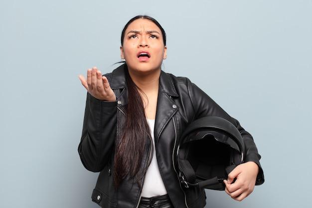 Donna ispanica che sembra disperata e frustrata, stressata, infelice e infastidita, gridando e urlando