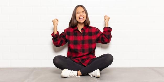 Donna ispanica che sembra estremamente felice e sorpresa, celebrando il successo, gridando e saltando