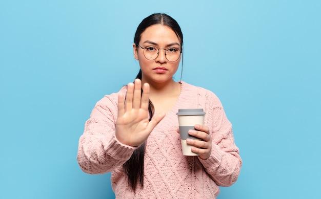 Donna ispanica che sembra seria, severa, dispiaciuta e arrabbiata che mostra la palma aperta che fa il gesto di arresto