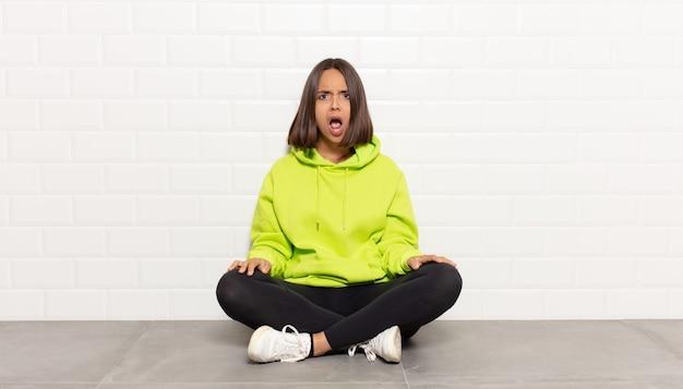 Donna ispanica che sembra scioccata, arrabbiata, infastidita o delusa, a bocca aperta e furiosa