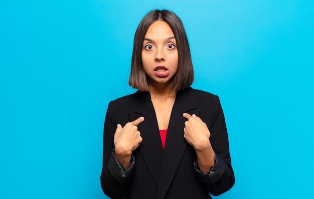 Donna ispanica che sembra scioccata e sorpresa con la bocca spalancata, indicando se stesso