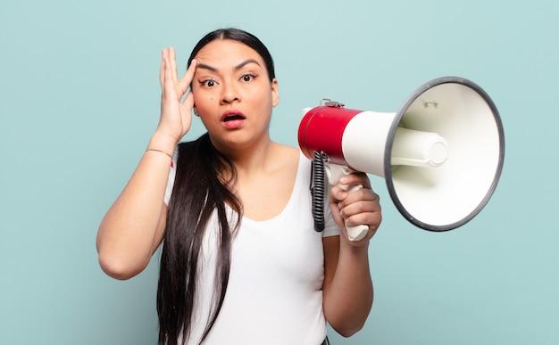 Donna ispanica che sembra sorpresa, a bocca aperta, scioccata, realizzando un nuovo pensiero, idea o concetto