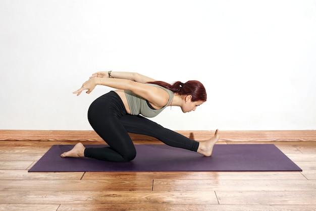 Donna ispanica che esegue le pose di yoga