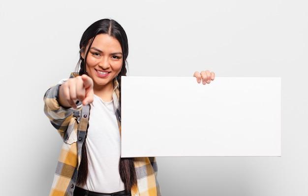 Donna ispanica che punta alla telecamera con un sorriso soddisfatto, fiducioso, amichevole, scegliendo te