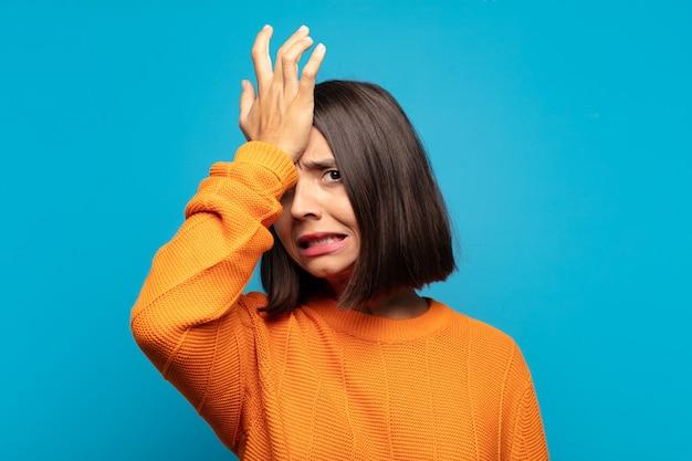 Donna ispanica che alza il palmo alla fronte pensando oops, dopo aver commesso uno stupido errore o ricordando, sentendosi stupida