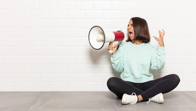 Donna ispanica che grida con le mani in alto, sentendosi furiosa, frustrata, stressata e sconvolta