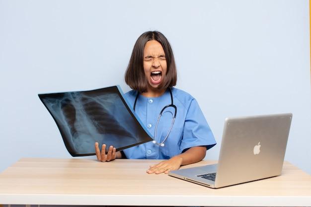 Donna ispanica che grida in modo aggressivo, sembra molto arrabbiata, frustrata, indignata o infastidita, urlando no