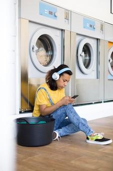 Donna ispanica seduta sul pavimento ascoltando musica nella lavanderia self-service.
