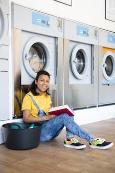 Donna ispanica seduta sul pavimento a leggere nella lavanderia self-service.