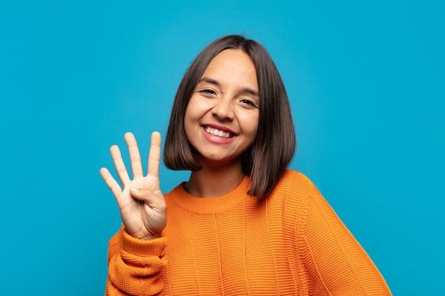 Donna ispanica sorridente e dall'aspetto amichevole, che mostra il numero quattro o il quarto con la mano in avanti, il conto alla rovescia