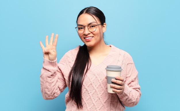 Donna ispanica sorridente e dall'aspetto amichevole, mostrando il numero quattro o il quarto con la mano in avanti