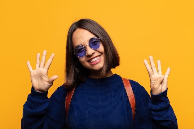 Donna ispanica sorridente e dall'aspetto amichevole, che mostra il numero nove o nono con la mano in avanti, il conto alla rovescia