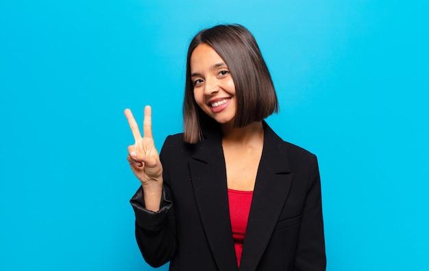 Donna ispanica sorridente e dall'aspetto amichevole, che mostra il numero due o il secondo con la mano in avanti
