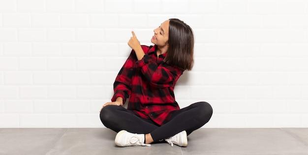 Donna ispanica in piedi e che punta a un oggetto sullo spazio della copia, vista posteriore