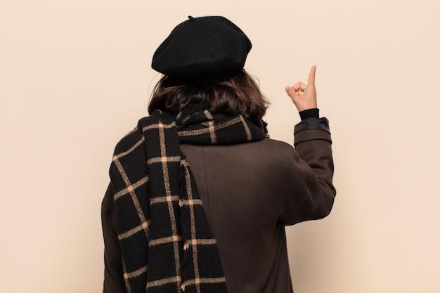 Donna ispanica in piedi e indicando un oggetto sullo spazio della copia