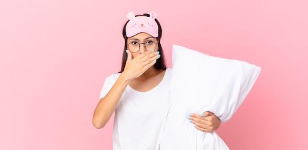 Donna ispanica che indossa un pigiama che copre la bocca con le mani con uno shock e tiene un cuscino