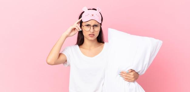 Donna ispanica che indossa un pigiama che si sente confusa e perplessa, mostra che sei pazzo e tiene in mano un cuscino