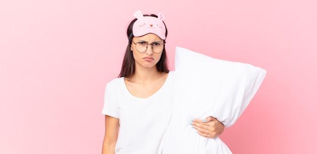 Donna ispanica che indossa un pigiama che si sente perplessa e confusa e tiene in mano un cuscino