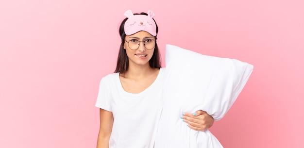 Donna ispanica che indossa un pigiama che sembra perplessa e confusa e tiene in mano un cuscino