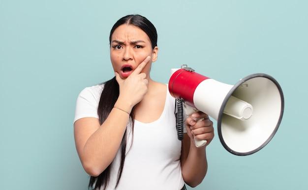 Donna ispanica con la bocca e gli occhi spalancati e la mano sul mento, che si sente spiacevolmente scioccata, dice cosa o wow