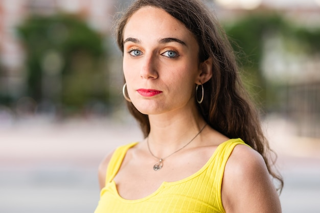 Ritratto ispanico della giovane donna all'aperto che guarda l'abbigliamento casual giallo del colpo alla testa della macchina fotografica