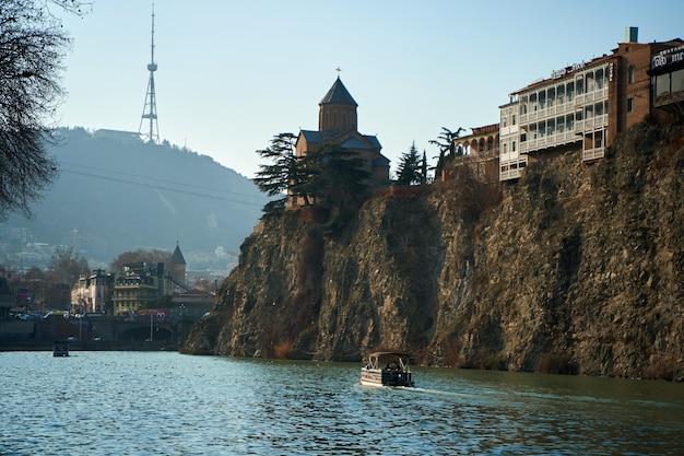 Storica chiesa di metekhi su una scogliera vicino al fiume kura a tbilisi. una barca da diporto sta navigando lungo il fiume.