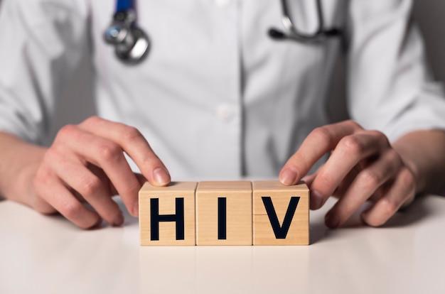 Iscrizione di acronimo di hiv sui dadi nelle mani del medico.