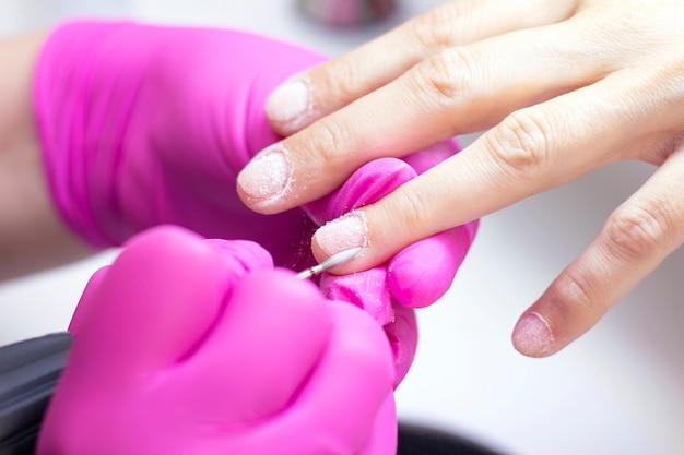 Un hmanicurist in guanti rosa manicure una ragazza