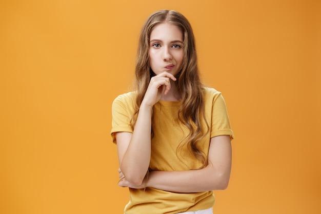 Hmm scelte difficili. ritratto di messa a fuoco giovane donna creativa dall'aspetto serio con capelli ondulati che sogghigna tenendo la mano sul mento in posa premurosa, prendendo una decisione, pensando su sfondo arancione.
