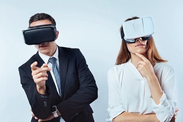 Hmm. mezzo busto di uomini d'affari che indossano occhiali per realtà visiva 3d e pensano a qualcosa di serio sullo sfondo.