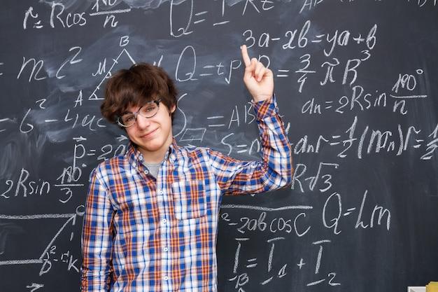 Un bel ragazzo con gli occhiali, la lavagna piena di formule matematiche