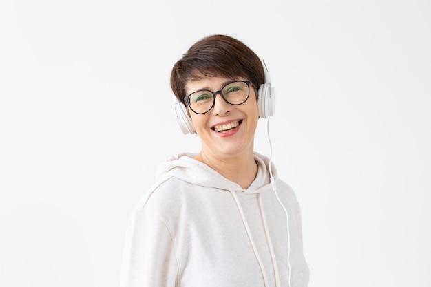 Hobby, interessi e concetto di persone - musica d'ascolto di bella donna 40-50 anni in grande cuffia sul muro bianco.