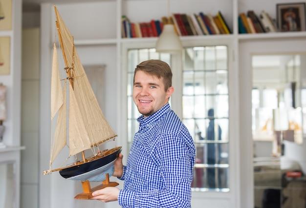 Hobby, interni e concetto di collezionismo - bell'uomo che tiene il layout di una barca a vela nella stanza