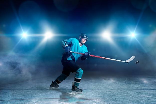 Il giocatore di hockey con bastone e disco fa un tiro