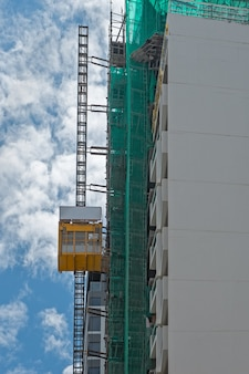 Piattaforma di sollevamento per il trasporto di passeggeri e materiale in un cantiere edile. gabbia dell'ascensore della costruzione.
